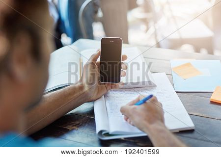 Rear View Of Unrecognizable Dark-skinned Student Holding Smart Phone With Blank Copy Space Screen Fo
