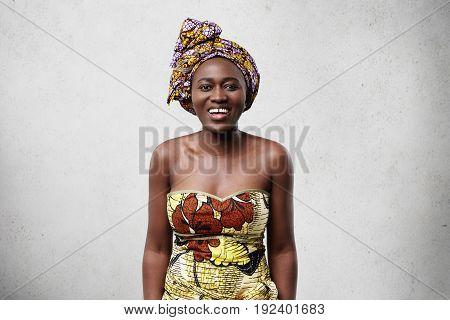 Portrait Of Glad Dark-skinned Woman With Big Dark Eyes, Thick Eyebrows Smiling Broadly Demonstrating