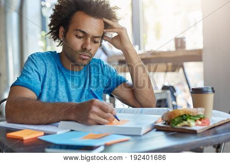 Concentrated Serious Afro American College Student With Beard Doing Home Assignment, Preparing For S