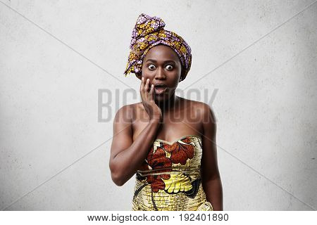 Indoor Image Of Dark-skinned African Woman Wearing Traditional Clothes Having Stupefaction Look. Sur