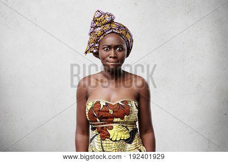Desperate Dark-skinned Woman In Elegant Dress And Scarf Pressing Her Lips Being Nervous. Black Beaut