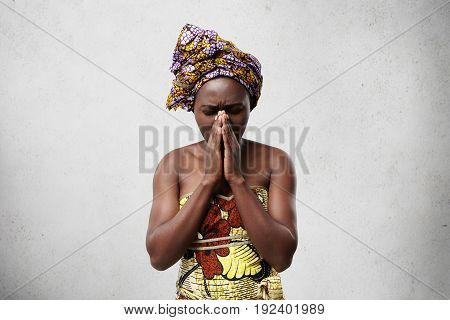 Portrait Of Begging Black Woman In Traditional Clothes Pressing Her Palms Together Closing Her Eyes