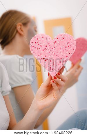 Woman Having Grey Face Mask Holding Heart Sponge