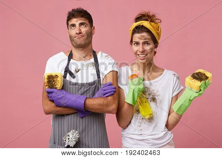 Husband Wearing Apron And Gloves Holding Sponge Looking Fatigued Up After Helping His Wife To Clean