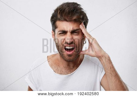 Portrait Of Depressed Male With Thick Beard Holding His Hand On Head Having Headache Being Sad After