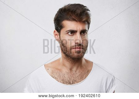 Portrait Of Handsome Guy With Brown Eyes, Trendy Hairdo And Beard Looking Seriously Aside Having Ang