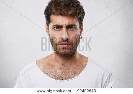 Close Up Portrait Of Serious Gloomy Bearded Man With Stylish Hairstyle Posing Against White Backgrou