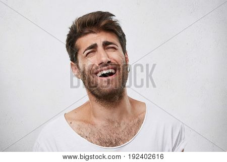 Bearded Man With Thick Eyebrows, Fashionable Hairstyle And Beard Bursting Into Laughing After Hearin