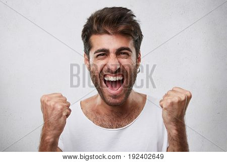 Positive Emotions, Victory, Triumph, Happiness Concept. Indoor Shot Of Happy Man With Beard Dressed