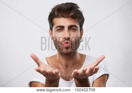 Attractive Macho Man With Dark Hair And Beard Blowing Kiss To You And Holding Hands In Front Of Hims