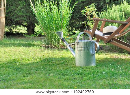 watering can and deck chair in a countryside garden