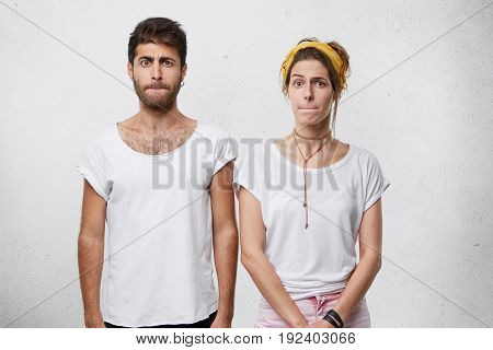 Young Couple In White T-shirts Standing Close To Each Other Pressing Their Lips With Displeasure Hav