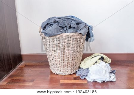 Clothes in a laundry wooden basket.The dirty clothes are not washed out of the basket.