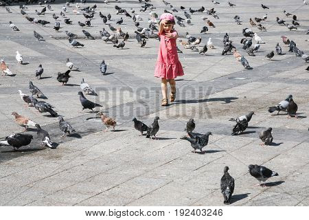 travel to Greece - girl chasing pigeons on urban square in Athens city