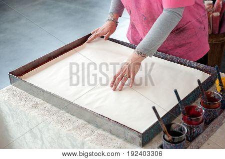 The artisan creates the typical handmade Florentine paper