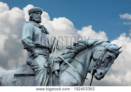 Giuseppe Garibaldi the Hero of Two Worlds equestrian statue with blue sky and clouds on background