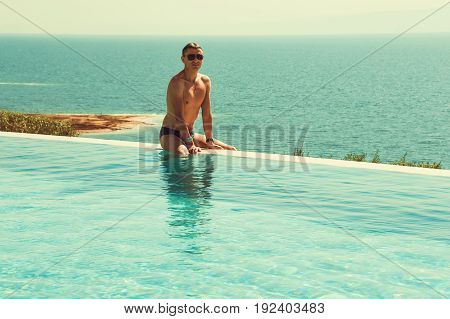 Successful rich man relaxing in infinity pool and enjoy vacation. Spa resort. Luxury lifestyle. Body care concept. Dead Sea view. Wealthy people. Tourism and travel. Copy space. Free time.