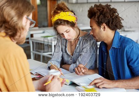 International Team Of Three Concentrated Casual Students Working On Common Research Over A Cup Of Co