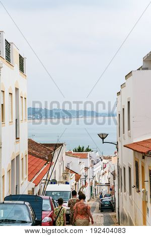Tourists On The Coastal Street In Lagos, Portugal