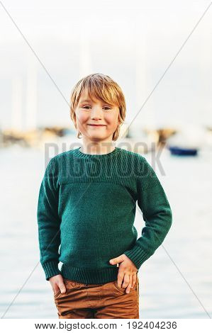 Fashion vertical portrait of adorable kid boy wearing green pullover