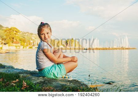 Sweet little girl resting by the lake on a nice sunny warm evening
