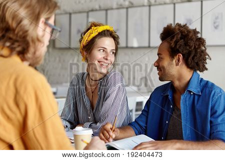 Portrait Of Beautiful European Student Female Looking With Smile At Her African Friend Discussing To
