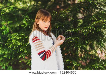 Outdoor portrait of cute 8-9 year old girl wearing white faux fur gilet. Kid playing with green prickly branches of a fur-tree or pine