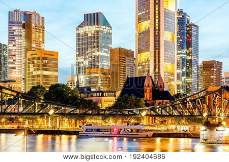 Beautiful cityscape view on the illuminated skyscrapers and bridge during the twilight in Frankfurt, Germany