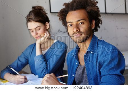Dark-skinned unshaven student with African hairstyle wearing blue shirt sitting near his groupmate female doing home assigment together. Female and male of different races being busy with studying
