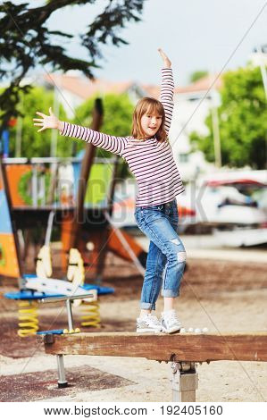 Adorable kid girl having fun on playground wearing stripe t-shirt and fashionable ripped jeans