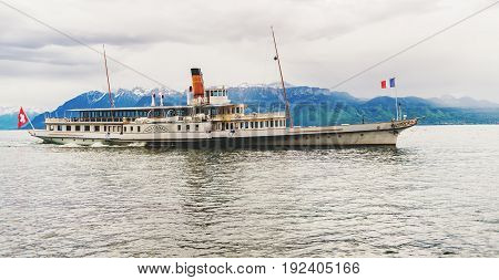 Steam boat with swiss and french flags floating on Lake Geneva or Lac Leman