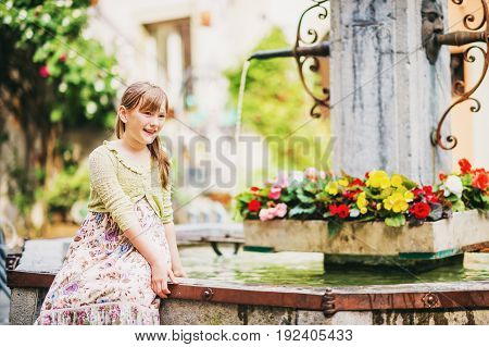 Outdoor portrait of adorable kid girl resting outdoors next to fountain on a very hot sunny day wearing long summer dress