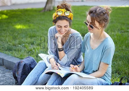 Two Females Sitting In Park With Books Learning New Material Helping Each Other Underline Main Infor