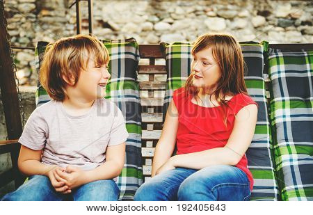 Two happy and laughing kids resting on swing bench