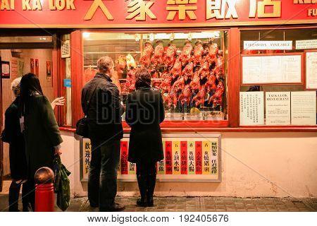 People Choose Food In Sidewalk Chinese Eatery