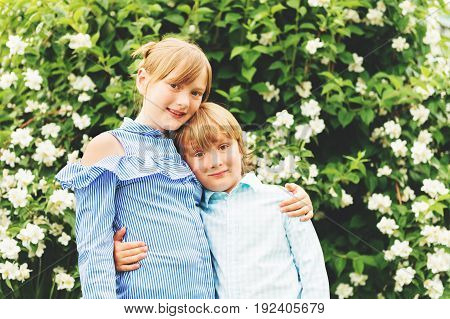 Two adorable kids playing together in spring garden wearing fashion shirts