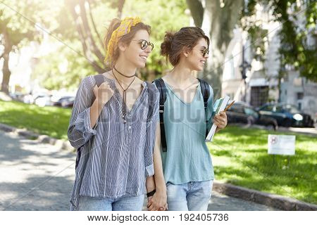 Cheerful Students Lesbians Walking Togehter Across Street Holding Hands Together Looking With Smile