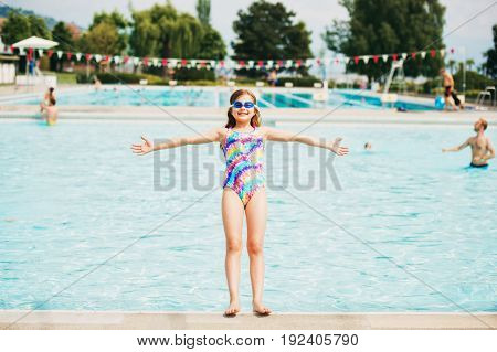 Little kid girl playing in outdoor swimming pool falling down into the water summer fun for children