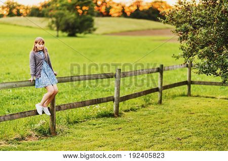 Pretty kid girl playing in a beautiful summer park at sunset resting on a fence happy childhood in countryside