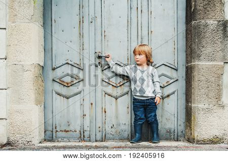 Outdoor portrait of cute 3 year old toddler boy wearing grey pullover