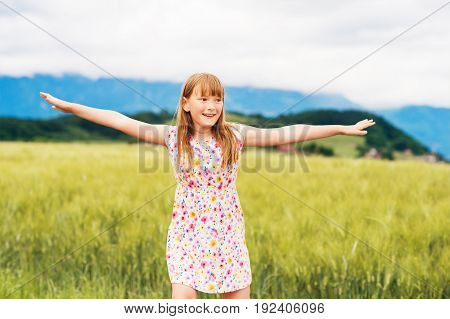 Little girl playing in green wheat field in summertime wearing a dress arms wide open