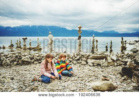 Kids playing between stacks of stones on the beach