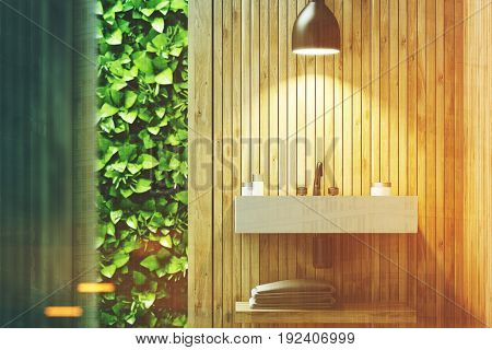 Eco bathroom interior with a narrow window green shrubbery is seen through it. There is a sink hanging on a wooden wall. 3d rendering mock up toned image