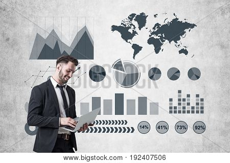 Young bearded businessman holding a laptop and standing near a concrete wall with ifographics and graphs drawn on it.