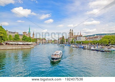 Panoramic view of historic Zurich city center with famous Grossmunster Fraumunster St. Peter church. Cruise vessel on river Limmat in front on a sunny day with clouds in summer Canton of Zurich Lake Zuerich Switzerland
