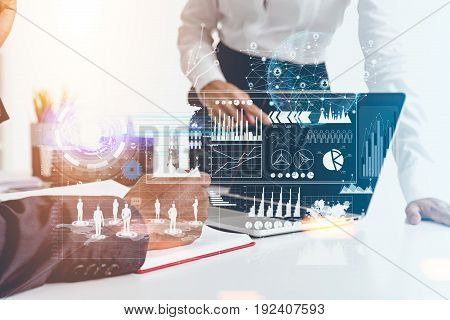 Close up of two unrecognizable business people working together in a white office. Graphs and diagrams in the foreground. Toned image double exposure mock up.