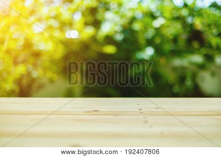 Wood table top on burred green natural background, selective focus and added color filter