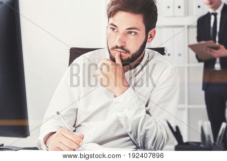 Portrait of a serious black haired young businessman looking at his computer screen and taking notes. Concept of planning. Toned image