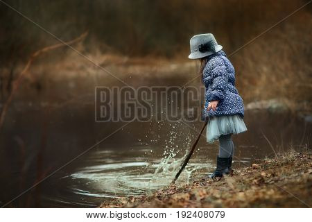 Girl  near river at spring cloudy day