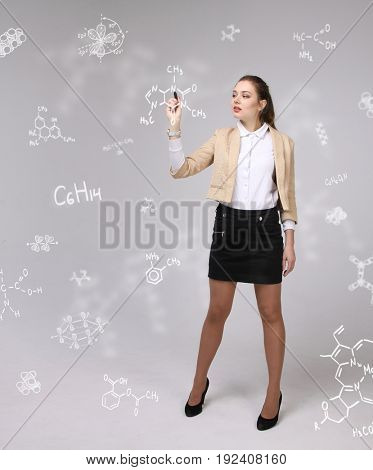 Woman chemist with stylus or pen working with chemical formulas on grey background.